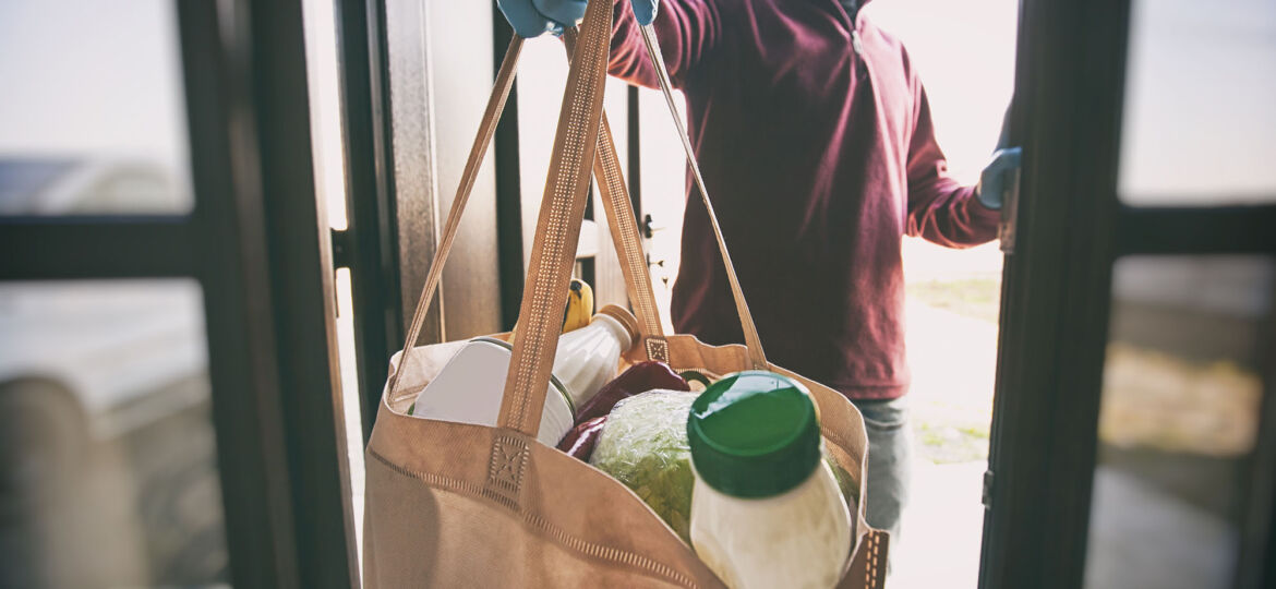 The delivery man gives the bag from grocery store to the woman t
